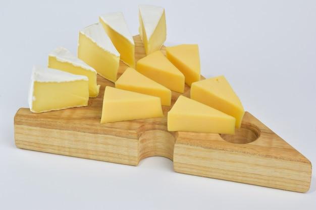 Mehrere stücke verschiedener käsesorten liegen auf einem speziellen holzständer für käse auf weißem clipping-hintergrund