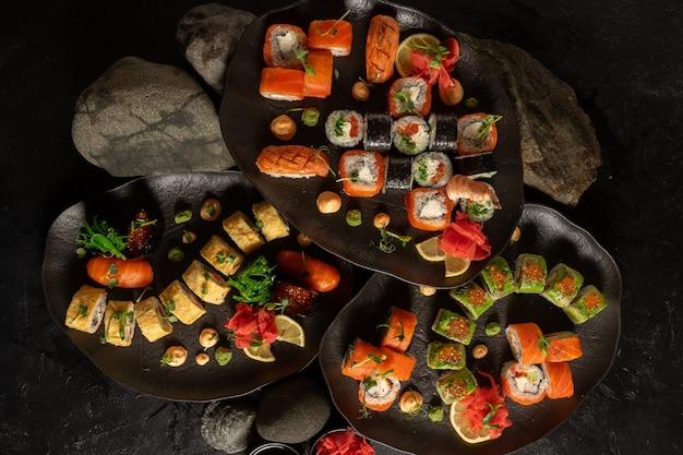 Mehrere sushi-sets aus der japanischen küche. sushi-rollen mit chuka-salat, lachs, philadelphia maki mit frischkäse, sashimi, gunkans mit rotem kaviar, avocado und japanischem tamago-omelett