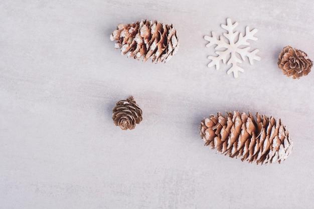 Mehrere tannenzapfen und schneeflocken auf weißem tisch.