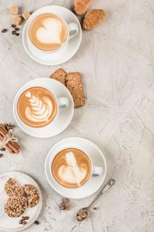 Mehrere tassen cappuccino-kaffee mit verschiedenen mustern auf dem schaum auf hellem hintergrund. draufsicht mit copyspace. restaurant essen.