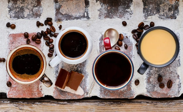 Mehrere tassen espresso, ristretto und mokka auf einer gemauerten fensterbank. draufsicht auf heißen kaffee, schokoladenkeile und kaffeekörner.