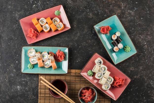 Mehrere teller mit sushi-rollen, die vom küchenchef auf dunklem hintergrund serviert werden. ansicht von oben mit einem kopierraum. restaurant essen. flach liegen