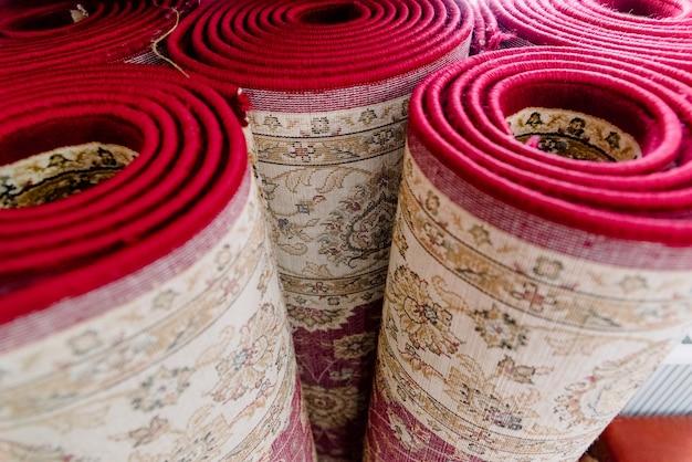 Mehrere teppiche in einer moschee rollten zur reinigung aufrecht