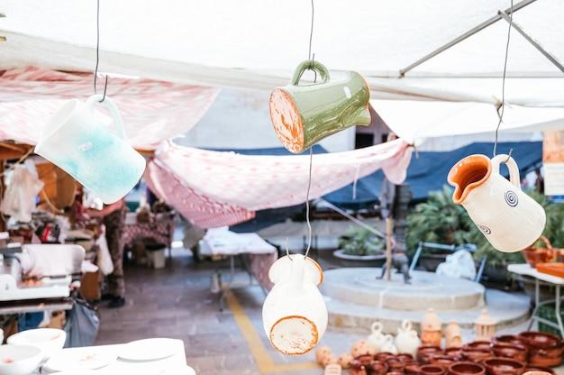 Mehrere tonkrüge hingen mit draht von einem stand auf einem lokalen flohmarkt.