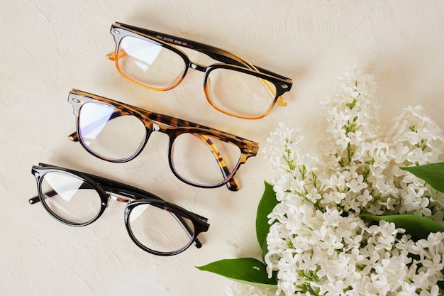 Mehrere verschiedene brillentrends und ein zweig aus weißem flieder auf strukturiertem beigefarbenem hintergrund, brillen und blumen kopieren raum