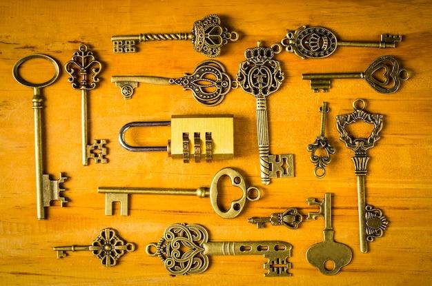 Mehrere vintage-schlüssel und kombinationsschloss auf holzbrett.