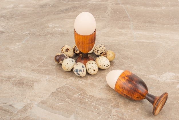 Mehrere wachteleier um weißes ei auf marmortisch herum.