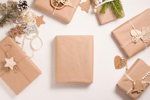 Mehrere weihnachtsgeschenkboxen im umweltfreundlichen stil auf weißem hintergrund, dekor aus weihnachtsbaumspielzeug aus holz, getrockneter orangen- und fichtenzweig, mock-up