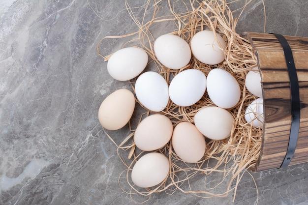Mehrere weiße frische eier auf heu auf marmorhintergrund. foto in hoher qualität