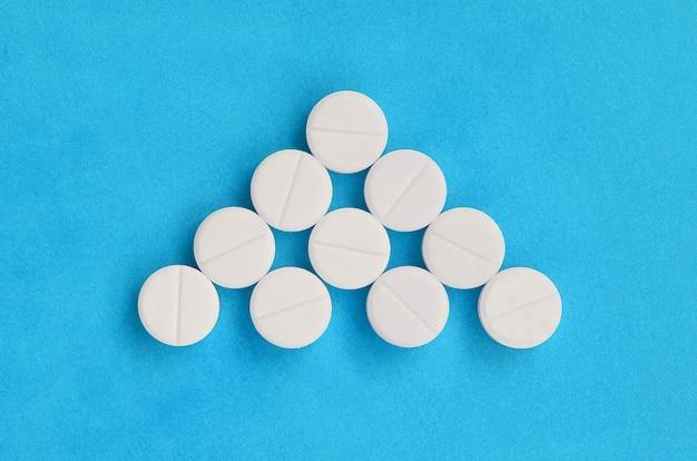 Mehrere weiße tabletten liegen in form eines dreieckigen pfeils auf hellem blau.