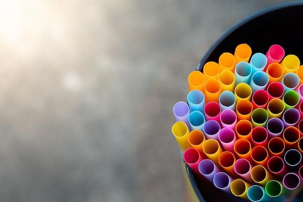 Mehrfache farbtrinkhalme in einer glasflaschenhintergrundunschärfe