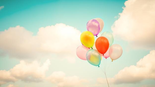Mehrfarbenballone der weinlese mit getan mit einem retro- instagram filtereffekt auf blauen himmel. ideen für den hintergrund der liebe im sommer und im valentinsgruß, hochzeitsflitterwochenkonzept.