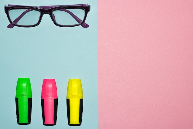 Mehrfarbenfilzstifte auf pastellrosa und blauem pastellhintergrund. bunte markierungen