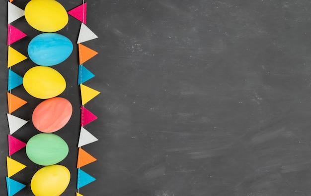 Mehrfarbig bemalte ostereier und filzgirlande auf kreidebrett copyspace