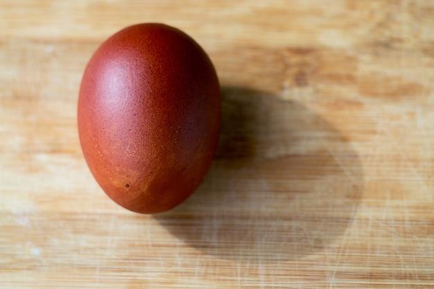 Mehrfarbig gefärbtes osterei mit schatten easter brown ei auf einem holzbrett closeup