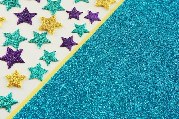 Mehrfarbig glänzende sterne auf grauem strukturiertem papier und einem streifen gelb und blau glänzendem papier