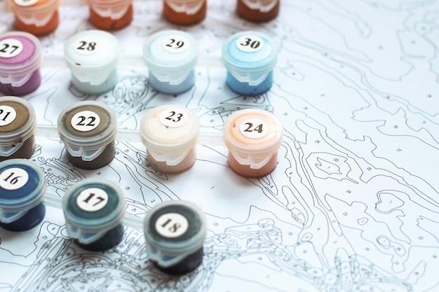 Mehrfarbige acrylfarben auf dem muster, das bilder nach zahlen zeichnet.