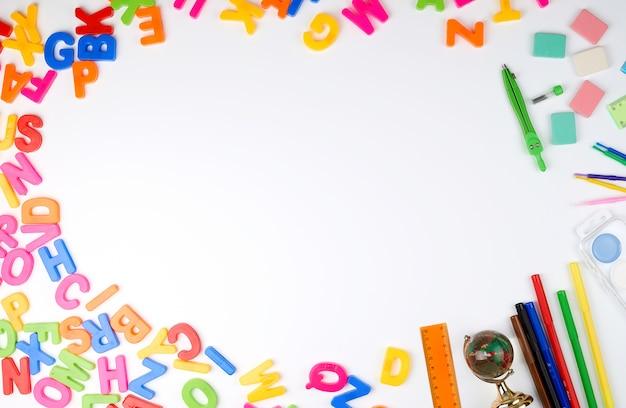 Mehrfarbige alphabetbuchstaben und schulbedarf