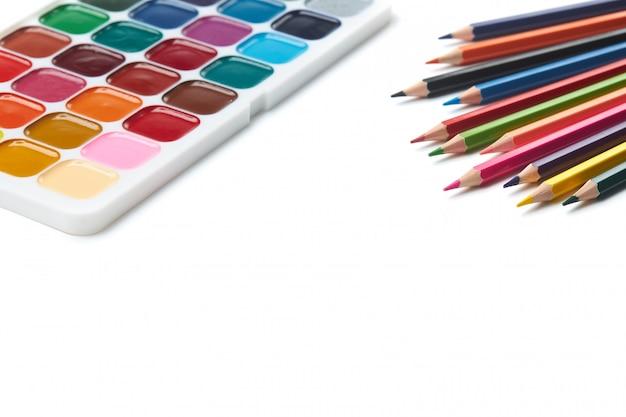 Mehrfarbige bleistifte und aquarellfarben liegen auf einem weißen hintergrund