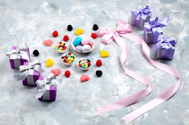 Mehrfarbige bonbons der draufsicht in kleinen tellern zusammen mit herzförmigen marmeladen und rosa schleifen der lila geschenkboxen auf dem regenbogen der grauen hintergrundgeburtstagszuckerfeier