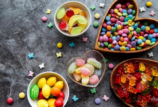 Mehrfarbige bonbons, dragees und gelee auf einer schwarzen oberfläche