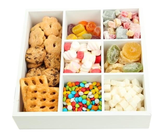 Mehrfarbige bonbons und kekse in der weißen holzkiste schließen oben