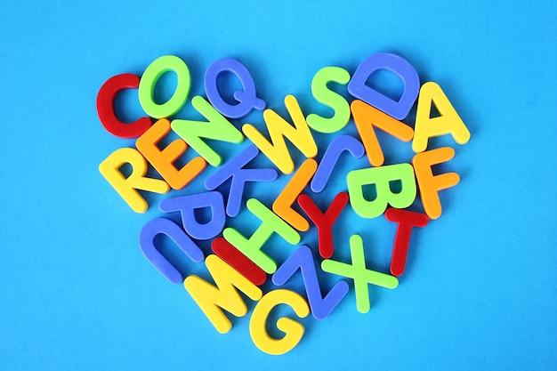 Mehrfarbige buchstaben des englischen alphabets werden in form eines herzens auf einen blauen hintergrund gelegt.