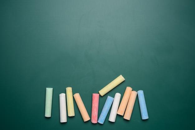 Mehrfarbige buntstifte auf grüner tafel
