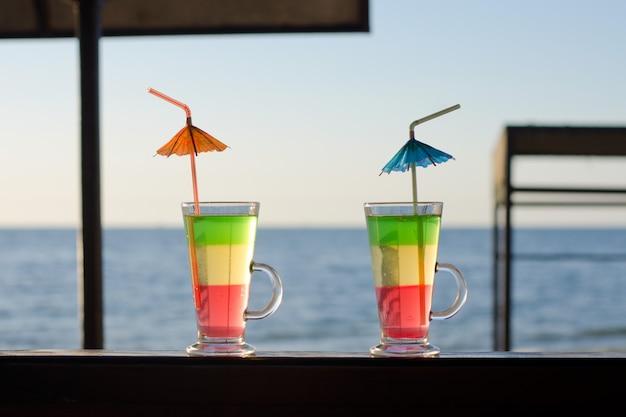 Mehrfarbige cocktails auf hölzerner aufnahme im hintergrund des meeres