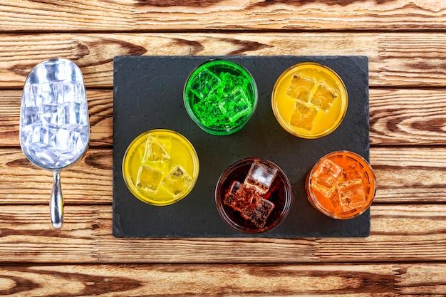 Mehrfarbige cocktails mit eis, fruchtsaft und alkohol auf einem steinständer. konzept: sommerliche auswahl an getränken an der bar, alkohol, alkoholischer cocktail