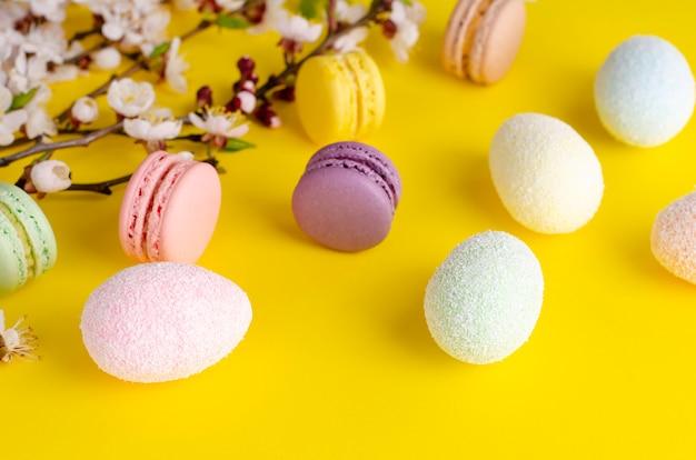 Mehrfarbige dekorative ostereier und süße macarons oder makronen verziert