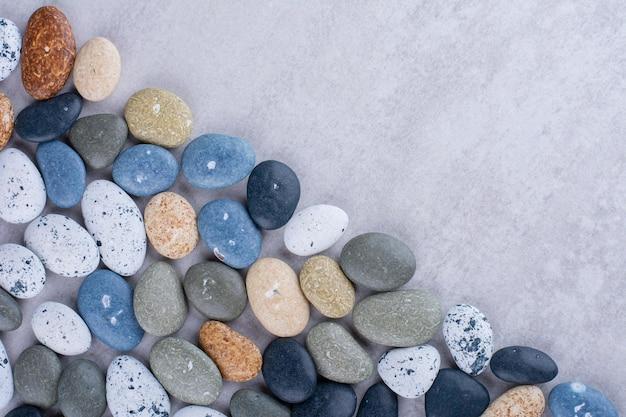 Mehrfarbige dekorative steine auf konkretem hintergrund isoliert. foto in hoher qualität
