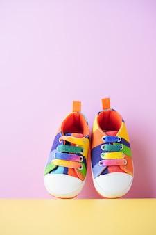Mehrfarbige denim-sportschuhe für babys, stehen auf rosa und gelbem hintergrund. das konzept der kinderbekleidung