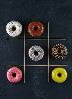 Mehrfarbige donuts mit glasur und streuseln auf einem tic-tac-toe-spiel mit schwarzem hintergrund.