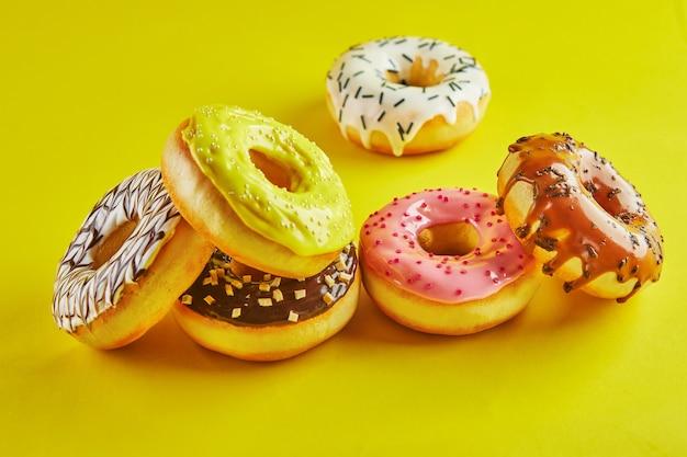 Mehrfarbige donuts mit glasur und streuseln auf gelbem grund.