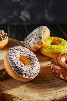 Mehrfarbige donuts mit glasur und streuseln auf hölzernen untersetzern auf schwarzem hintergrund.