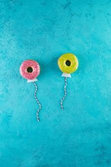 Mehrfarbige donuts mit glasur und streuseln in form von luftballons, die in den himmel fliegen.