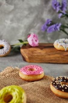 Mehrfarbige donuts mit glasur und streuseln mit blumen auf grauem hintergrund.