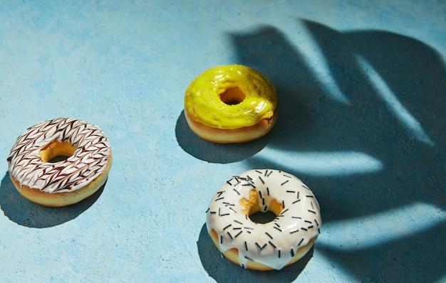 Mehrfarbige donuts mit zuckerguss, streusel mit schatten vom monstera-blatt auf blauem hintergrund.