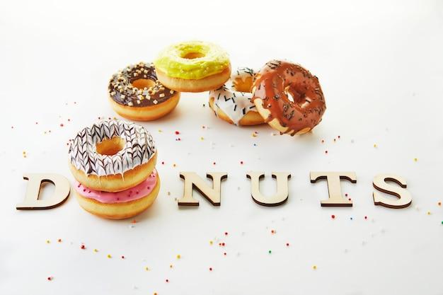 Mehrfarbige donuts mit zuckerguss, streuseln und den inschriften-donuts auf weißem hintergrund.