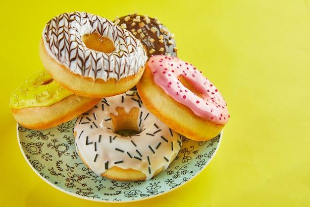 Mehrfarbige donuts mit zuckerguss und spritzern auf einem blauen teller auf gelbem grund.