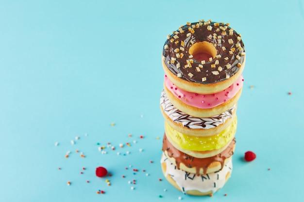 Mehrfarbige donuts mit zuckerguss und streuung gestapelt in einem stapel auf blauem hintergrund.
