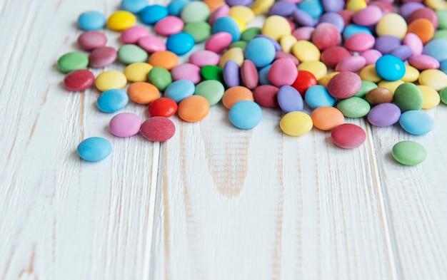 Mehrfarbige dragee-süßigkeiten auf einer weißen holzoberfläche