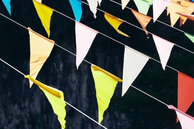 Mehrfarbige dreieckige flaggen, die an den seilen auf einem dunklen hintergrund hängen