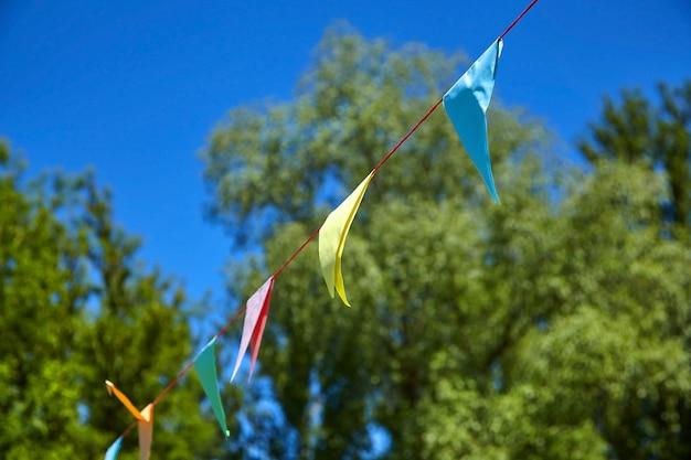 Mehrfarbige dreieckige papierfestivalflaggen auf blauem himmel und grünen bäumen