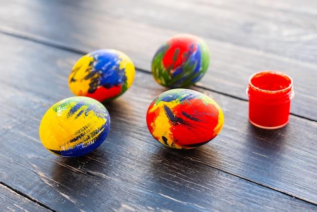 Mehrfarbige eier, farben und bürste ostern auf einer tabelle. vorbereitung für einen urlaub