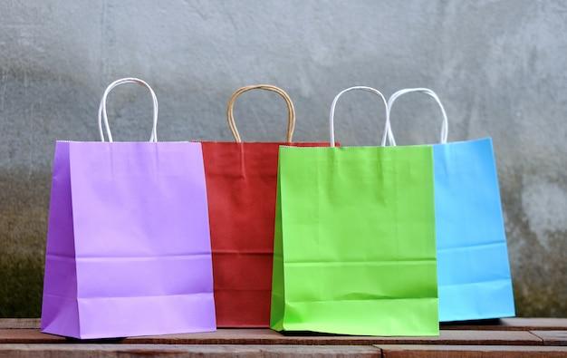 Mehrfarbige einkaufstaschen auf einem holztisch platziert, für die werbung.