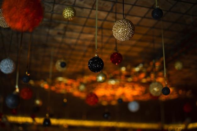 Mehrfarbige, erstaunlich schöne neujahrsspielzeuge hängen an einer vintage-luxusdecke in einem restaurant. weihnachtsdekorationen. vorbereitung auf das neue jahr. guter neujahrsgeist