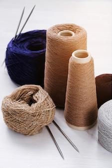 Mehrfarbige fäden, stränge und verwicklungen aus italienischem wollgarn, stricknadeln. das konzept des strickens, handarbeit, handgemacht.