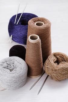 Mehrfarbige fäden, stränge und verwicklungen aus italienischem wollgarn, stricknadeln.